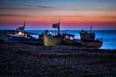 Рыбацкие лодки ждать быть запущенным от пляжа Hastings перед рассветом стоковые изображения rf