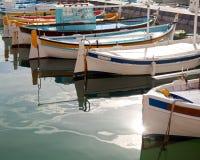 Рыбацкие лодки на воде в солнечности с отражением Стоковая Фотография