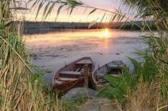 Рыбацкие лодки на реке на заходе солнца Стоковые Изображения