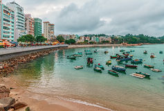 Рыбацкие лодки отдыхают в заливе Стэнли seashore на предпосылке зданий Красивый сценарный ландшафт портового района Стэнли Стоковое Изображение RF