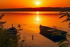 2 рыбацкой лодки причалили около берега пруда на фоне захода солнца тонизировано камера искусства красивейшая eyes способ полные  Стоковая Фотография RF