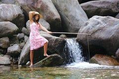 Рыбная ловля девушки страны в реке горы Стоковые Фото