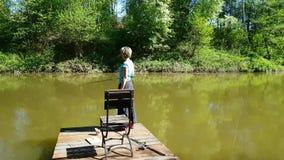Рыбная ловля женщины на пруде сток-видео