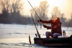 Рыбная ловля льда на щуке рыб задвижки рыболова замороженного озера усмехаясь Стоковое Фото