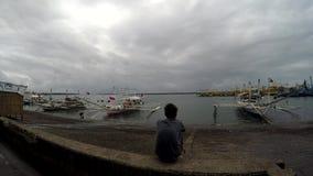 Рыбная ловля мальчика сидя наблюдая малая деревянная поставила на море порт на якорь видеоматериал