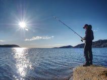 Рыбная ловля молодого человека на озере на заходе солнца Один человек с рыболовной удочкой стоит на скалистом береге Стоковые Изображения