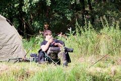 Рыбная ловля молодого человека рекой Стоковые Фотографии RF