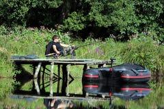 Рыбная ловля молодого человека рекой Стоковые Изображения RF