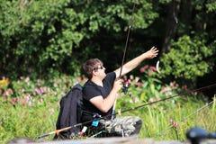 Рыбная ловля молодого человека рекой Стоковая Фотография RF