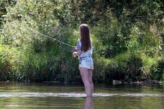 Рыбная ловля молодой женщины на реке в Германии Стоковое фото RF
