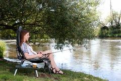 Рыбная ловля молодой женщины на реке в Германии Стоковая Фотография