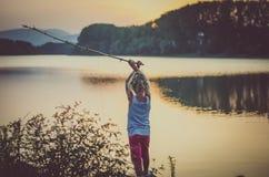 Рыбная ловля ребенка на озере на времени захода солнца стоковые фотографии rf