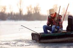Рыбная ловля человека сезона зимы на замороженном реке стоковое изображение