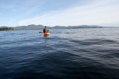 Рыбная ловля Kayaker в спокойной воде Стоковая Фотография RF