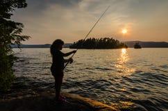 Рыбная ловля девушки на заходе солнца Стоковые Изображения