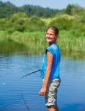 Рыбная ловля девушки на реке Стоковая Фотография RF