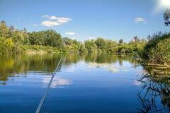 Рыбная ловля лета двигая под углом на солнечном свете озера ослабляет хобби Стоковые Фотографии RF