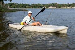 Рыбная ловля и Paddlng человека в каяке Стоковые Фото