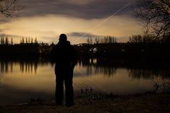 Рыбная ловля карпа двигая под углом на ноче с загоренными сигналами тревоги Стоковая Фотография