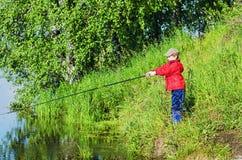 Рыбная ловля мальчика в утре лета Стоковые Изображения
