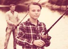 Рыбная ловля мальчика используя штангу от стороны воды Стоковые Фотографии RF