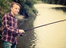 Рыбная ловля мальчика используя штангу от стороны воды Стоковое Изображение