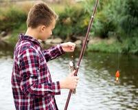 Рыбная ловля мальчика используя штангу от стороны воды Стоковое Изображение RF