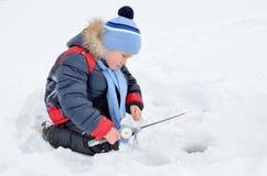 Рыбная ловля мальчика на замороженном реке в зиме Стоковое Фото