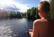 Рыбная ловля мальчика на озере Стоковая Фотография RF