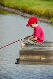 Рыбная ловля мальчика на доке Стоковая Фотография