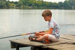 Рыбная ловля мальчика на пруде Стоковое Фото