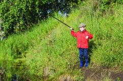 Рыбная ловля мальчика на пруде Стоковое Изображение RF