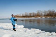 Рыбная ловля мальчика с штангой на реке в зиме Стоковые Фото