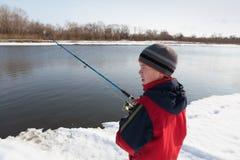 Рыбная ловля мальчика с штангой на реке в зиме Стоковое Изображение