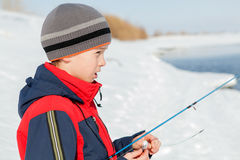 Рыбная ловля мальчика с штангой на реке в зиме Стоковые Изображения