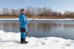 Рыбная ловля мальчика с штангой на реке в зиме Стоковое Изображение RF