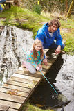 Рыбная ловля отца и дочери в пруде с сетью Стоковая Фотография RF