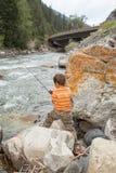 Рыбная ловля ребенка в реке Стоковые Фотографии RF