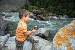 Рыбная ловля ребенка в реке Стоковые Изображения