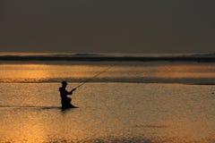 Рыбная ловля рыболова на заходе солнца или восходе солнца Стоковые Изображения