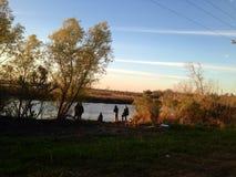 Рыбная ловля семьи на речном береге на заболоченном рукаве реки Стоковые Фотографии RF