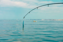 Рыбная ловля соленой воды - штанга с wobbler и голубой морской водой Стоковое Изображение