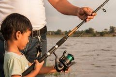 Рыбная ловля сына и папы на реке Стоковые Фото