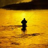 Рыбная ловля человека в реке рано утром Стоковые Изображения