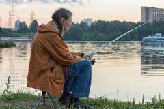 Рыбная ловля человека на рыболовной удочке Стоковые Изображения
