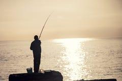 Рыбная ловля человека на утре Стоковые Изображения