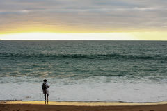 Рыбная ловля человека от берега на заходе солнца Стоковые Изображения