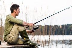 Рыбная ловля человека расслабляющая или двигать под углом на озере стоковые фотографии rf