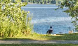 Рыбная ловля человека с собака Стоковые Изображения