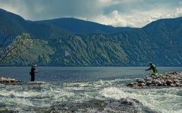 2 рыболова на рте реки которое пропускает в озеро на предпосылке гор Стоковое фото RF